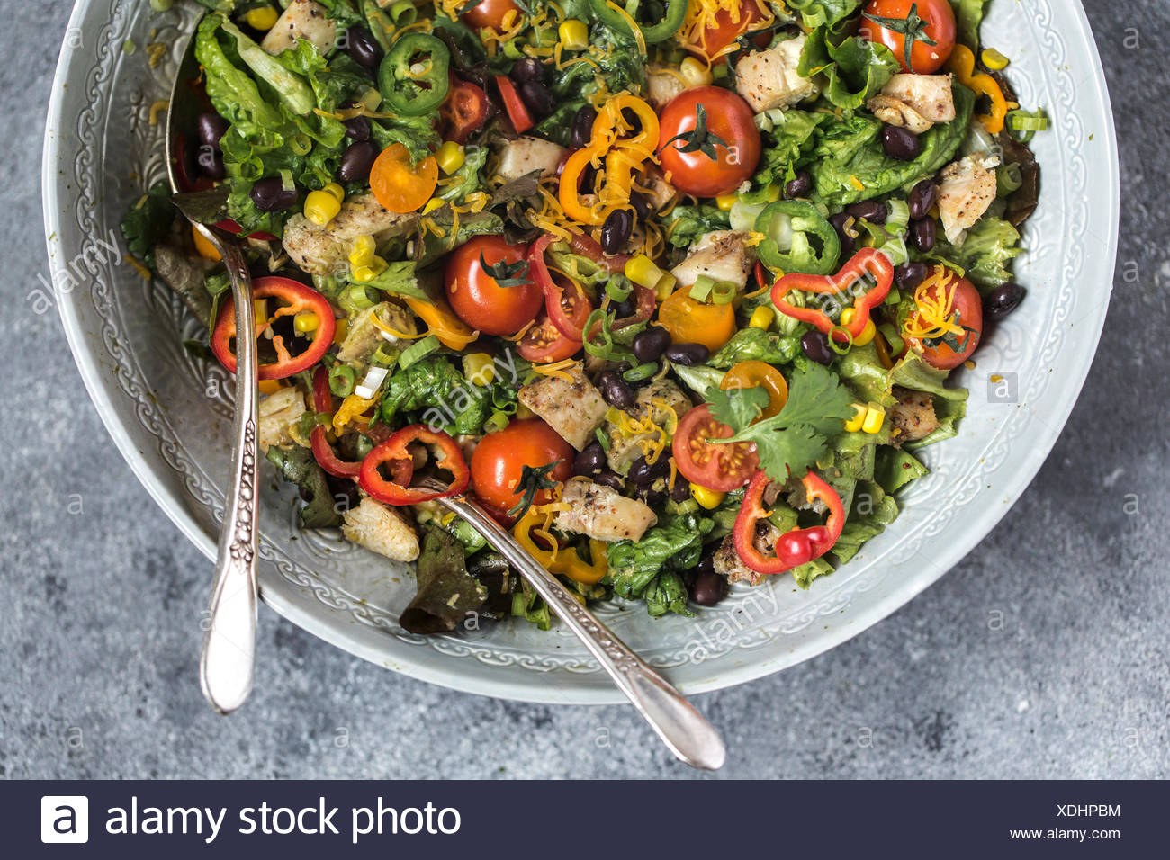A large bowl of Southwestern Chicken Salad with Creamy Avocado Dressing is photographed from the top view. - Stock Image