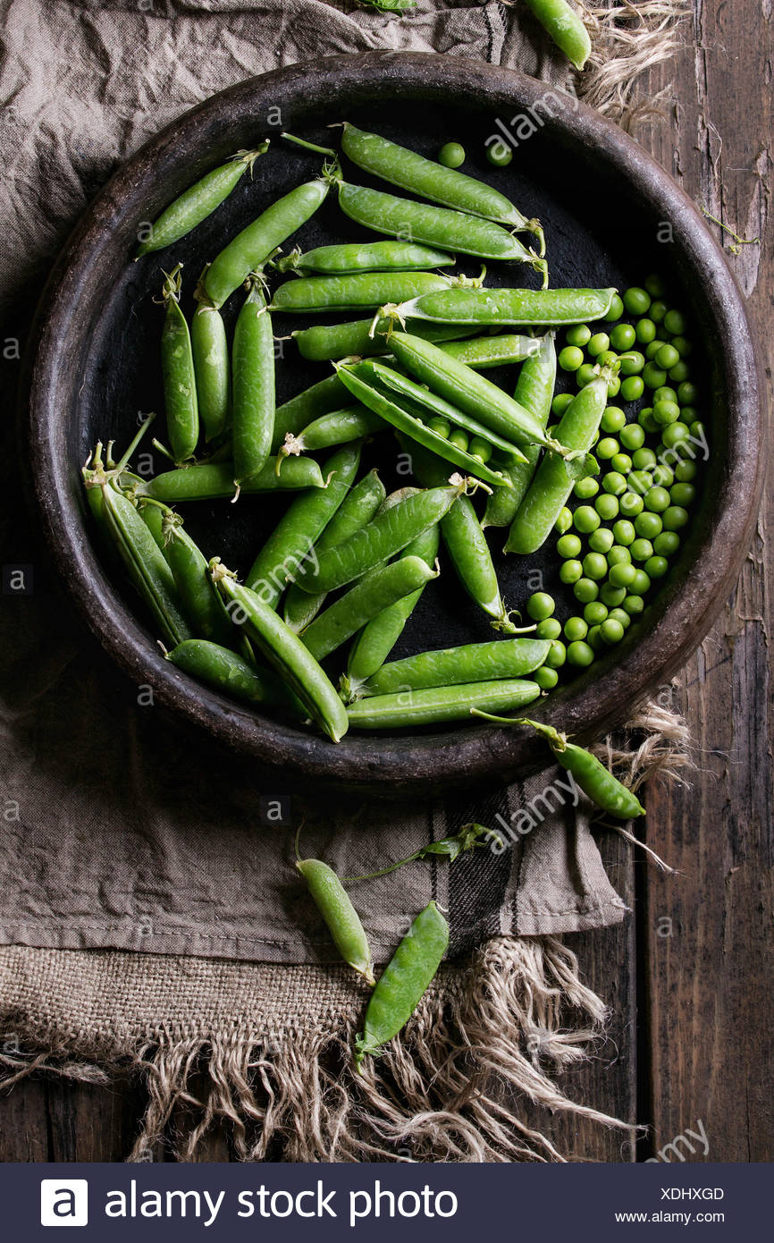 Young organic green pea pods and peas in terracotta tray over old dark wooden planks with sackcloth textile background. Top view with space. Harvest,  - Stock Image