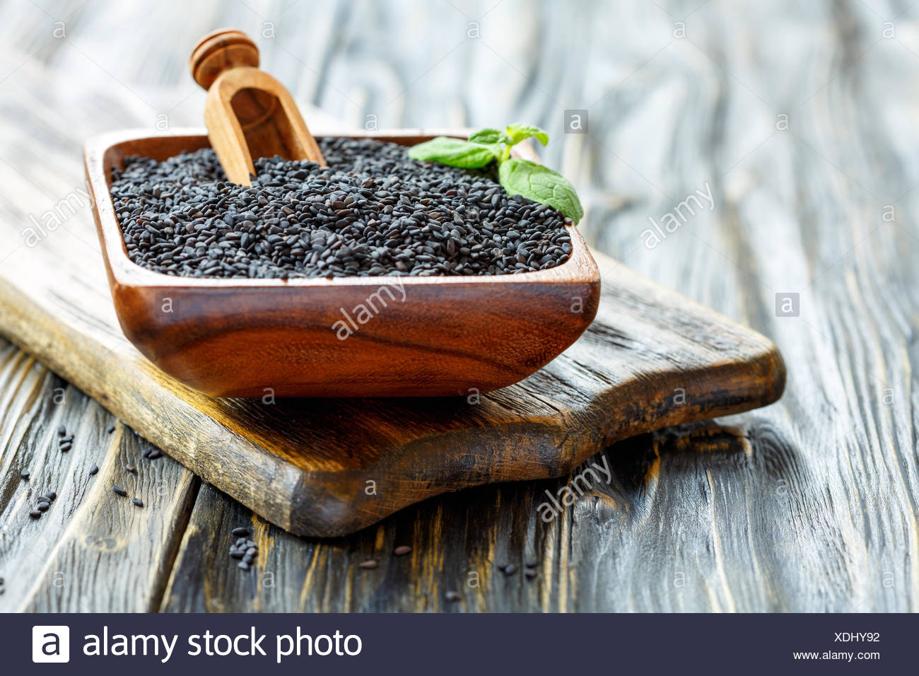Wooden bowl of black sesame seed and scoop. - Stock Image