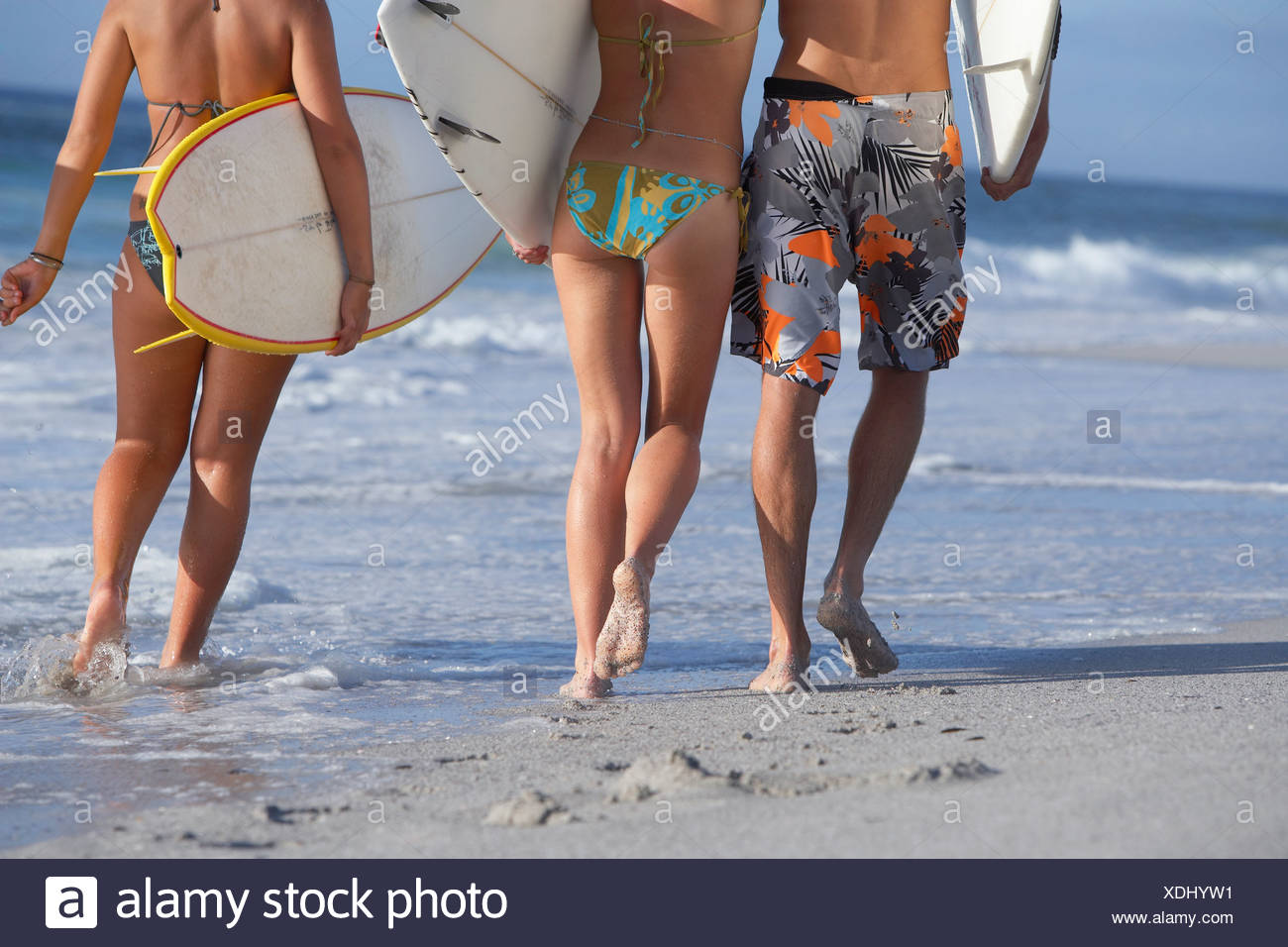 Two young women and man walking on beach carrying surfboards side by side low section rear view - Stock Image