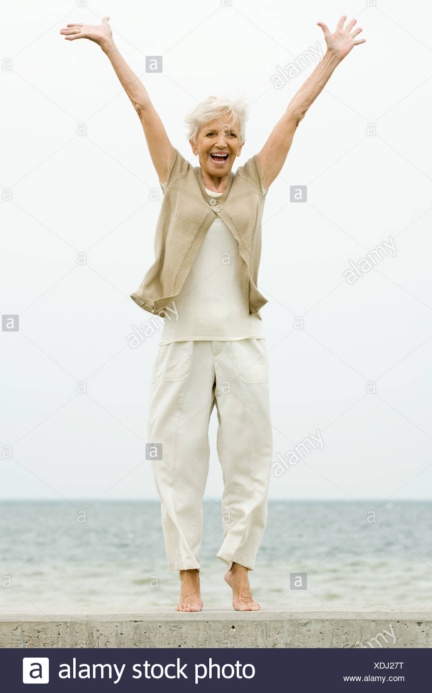 Senior woman standing on tiptoe at the beach, arms raised, smiling - Stock Image