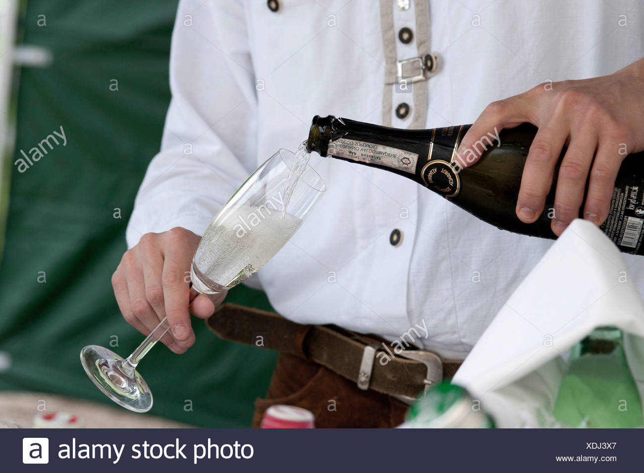 Man pouring a glass of champagne, sparkling wine or prosecco, close-up of hands Stock Photo