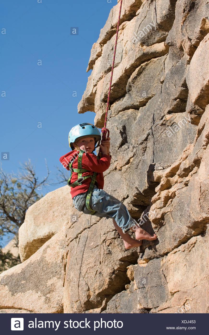 Boy rappelling cliff face, Joshua Tree National Park, California. - Stock Image
