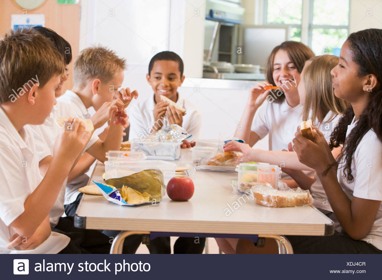 Students sitting at cafeteria table eating lunch (depth of field) - Stock Image