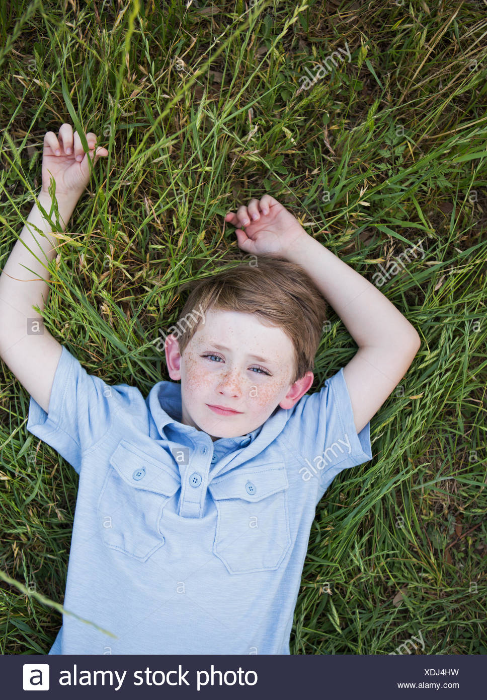 A Boy In A Blue Shirt Lying On His Back On Grass Stock