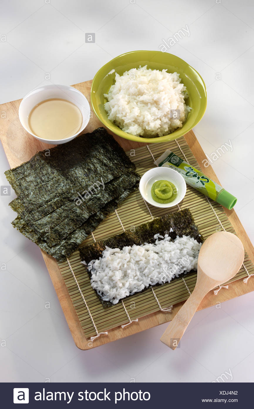 Spreading the rice onto the nori seaweed leaves - Stock Image