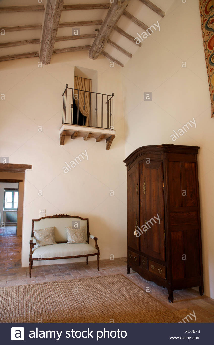 Large antique cupboard and French wood framed sofa on Italian country landing with a Juliet style balcony - Stock Image