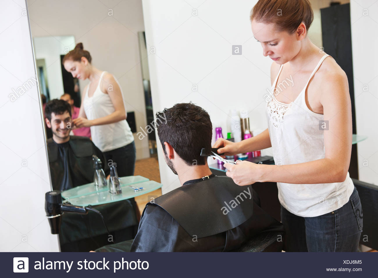 A female hairdresser cutting his male clients hair with scissors - Stock Image