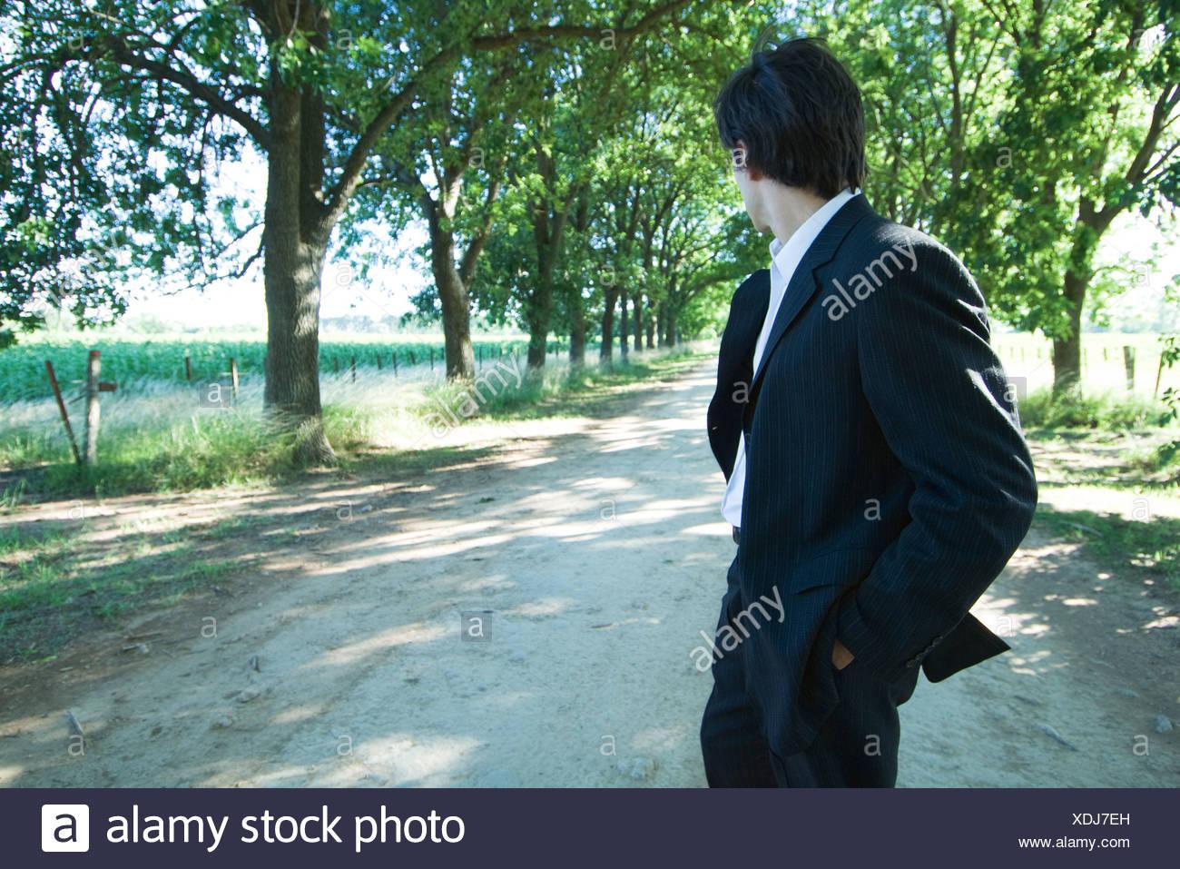 Businessman walking on rural road, looking over shoulder - Stock Image