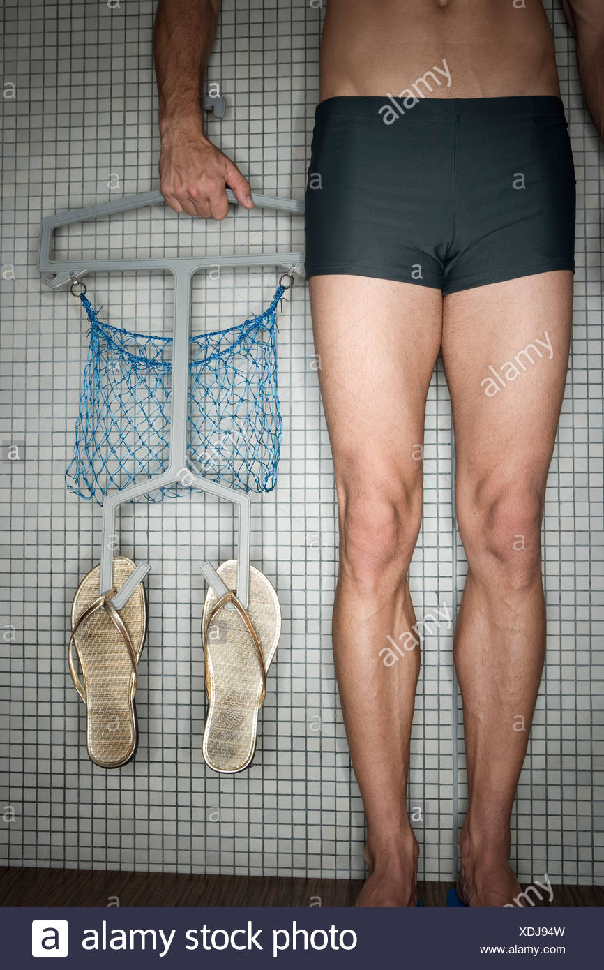 Man standing in changing room, holding hanger with flip-flops, low section - Stock Image