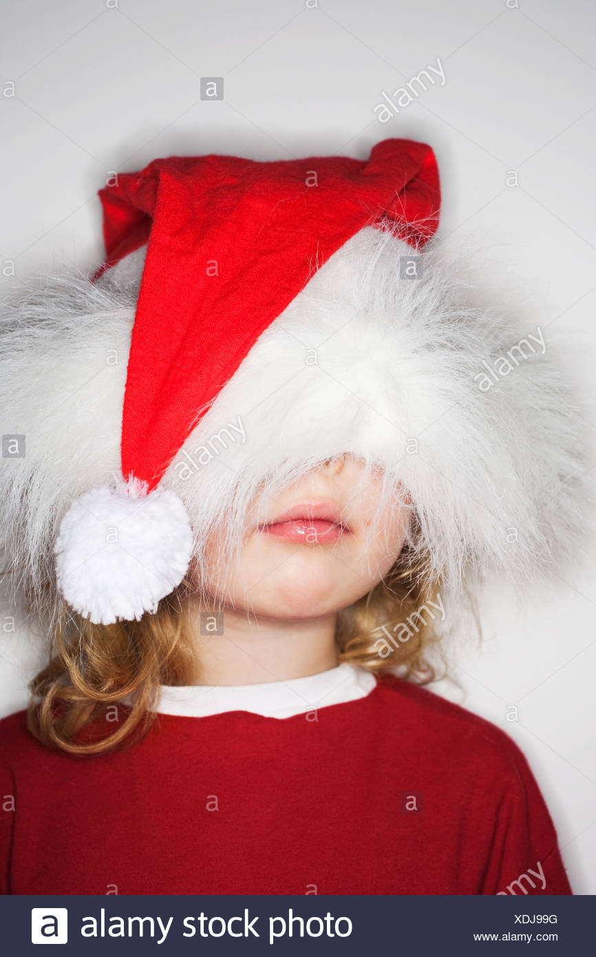 Girl wearing santa hat over head - Stock Image