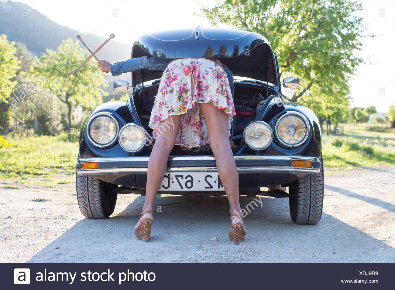 Mature woman bent over car, looking in bonnet - Stock Image