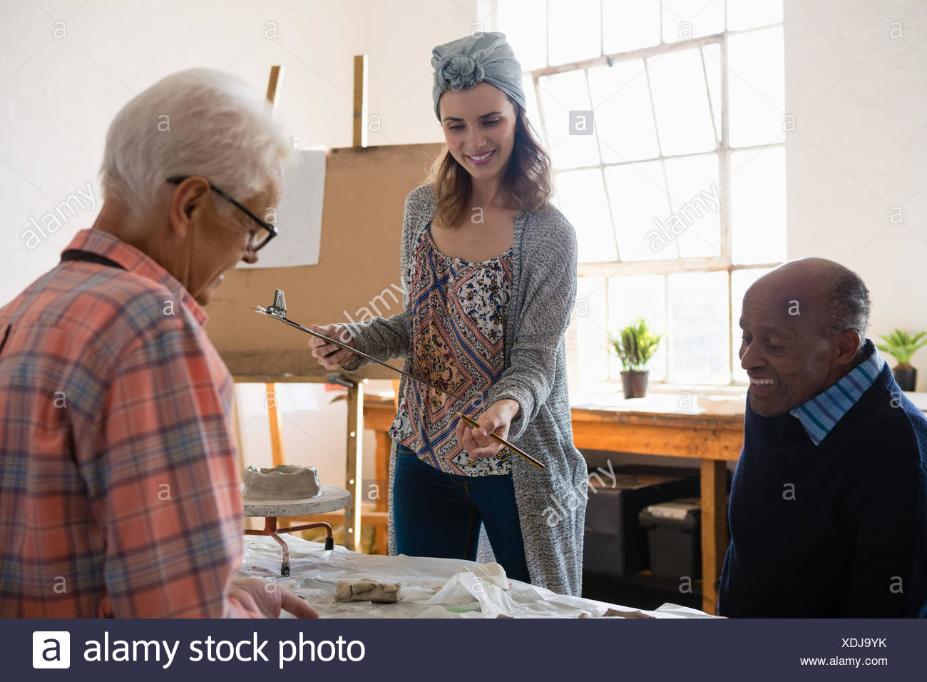 Smiling female holding clipboard while talking with male artists in art class - Stock Image