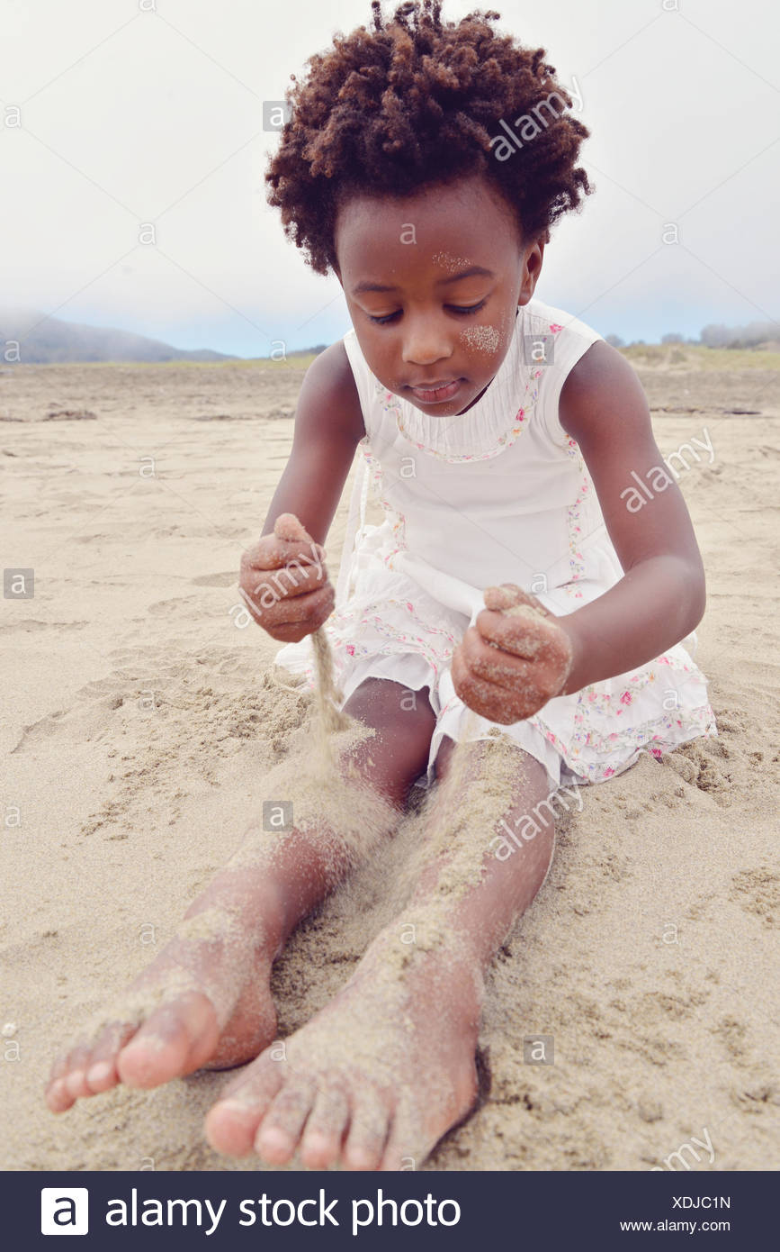 Girl sitting on a beach covering her legs with sand - Stock Image