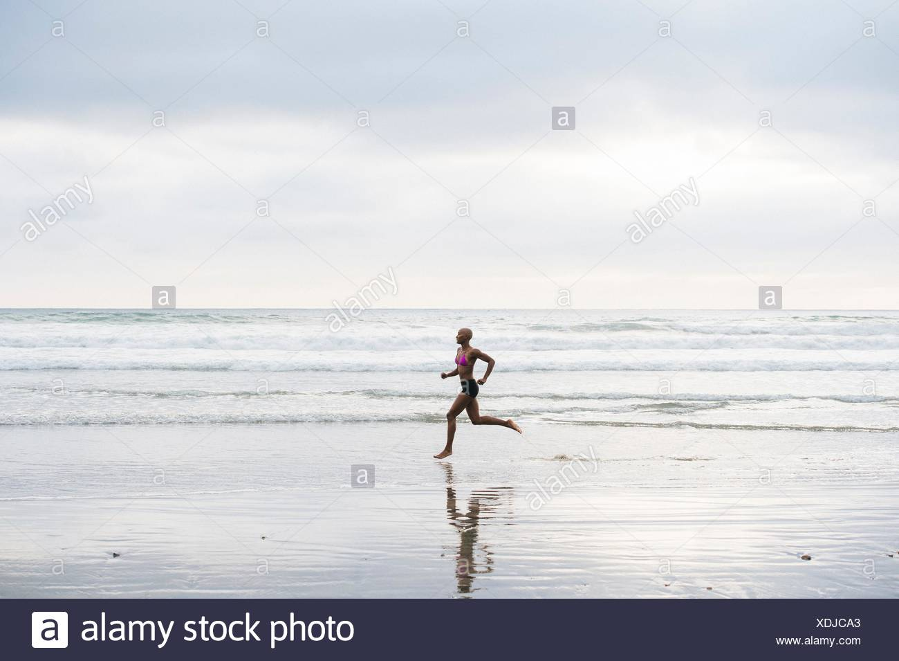 Woman in bikini jogging on beach - Stock Image