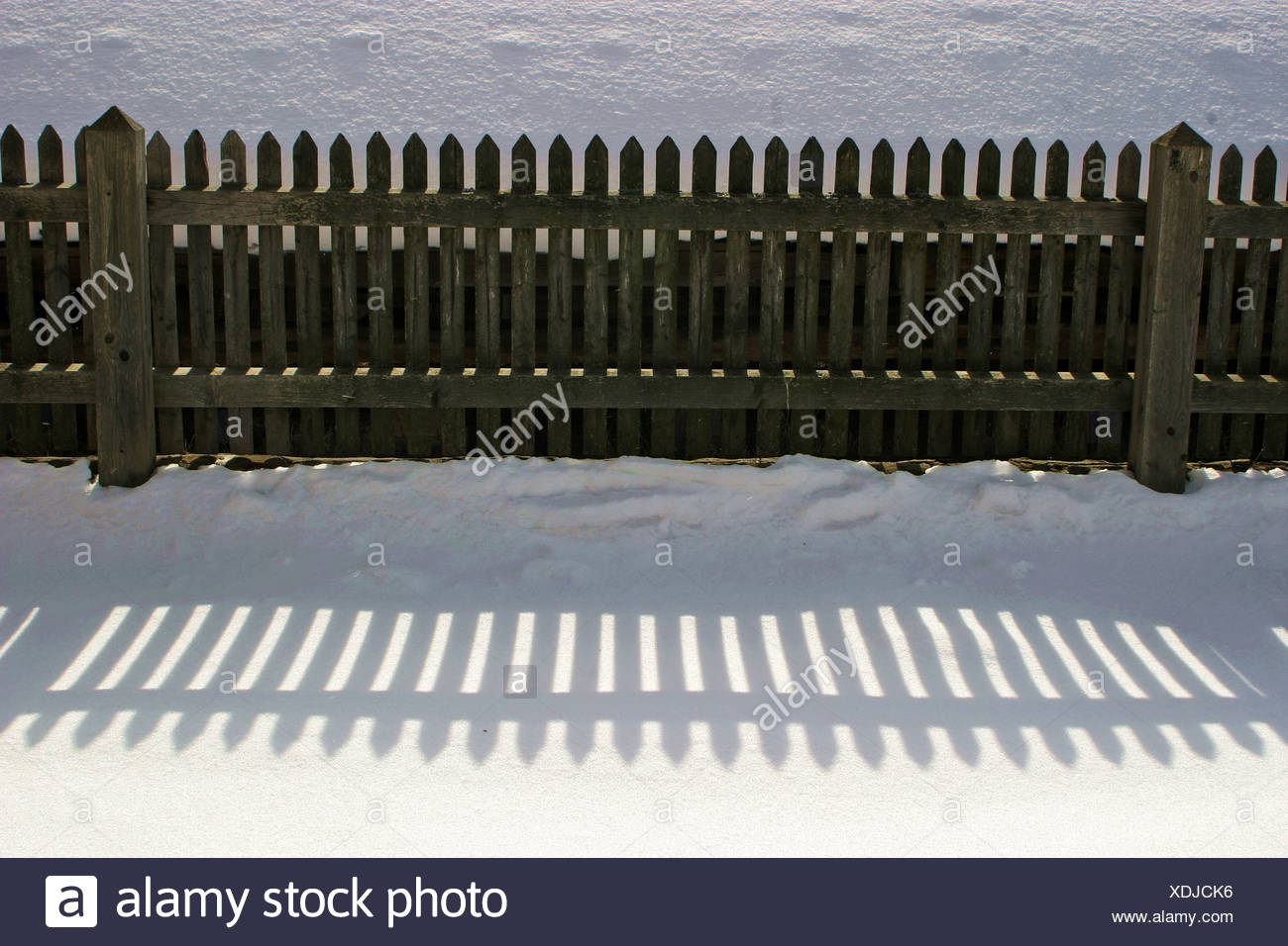 Wood-fence and shadow in snow - Stock Image