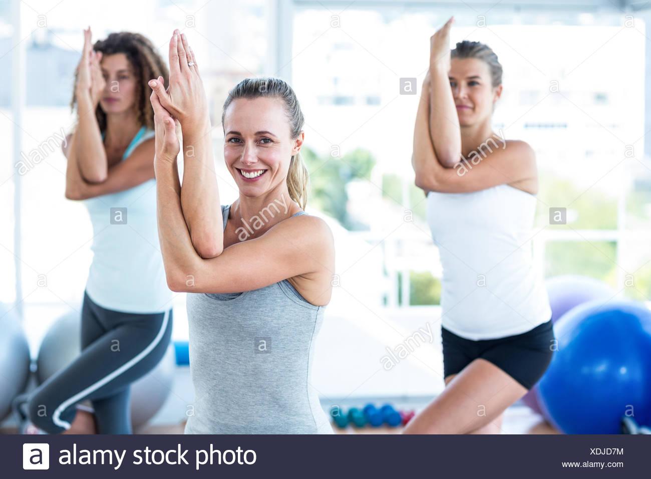 Beautiful women doing eagle pose - Stock Image