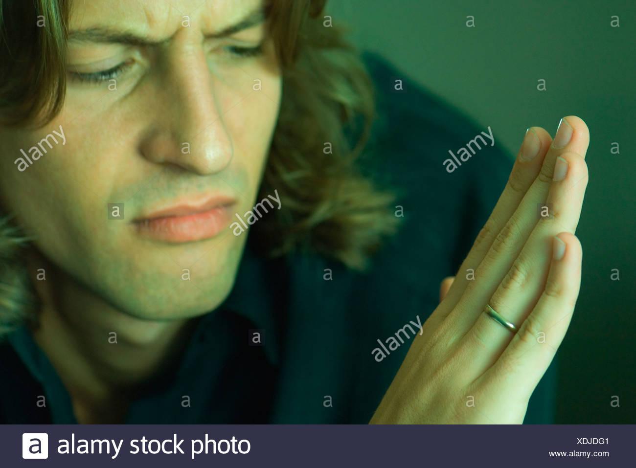 Man furrowing brow looking at own wedding ring - Stock Image