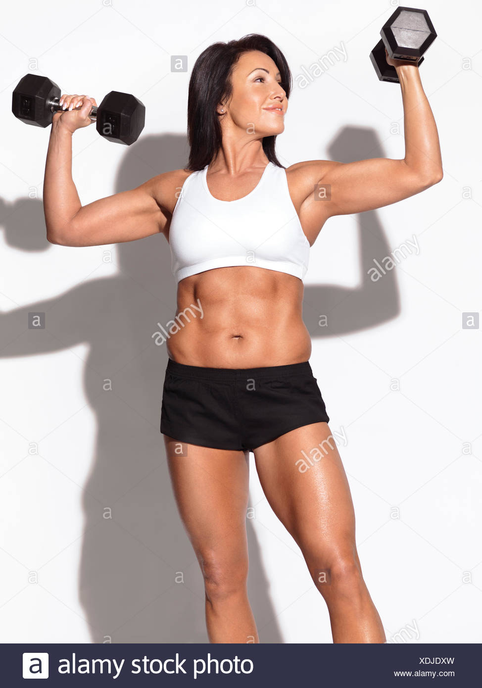 Fit woman holding dumbbells - Stock Image