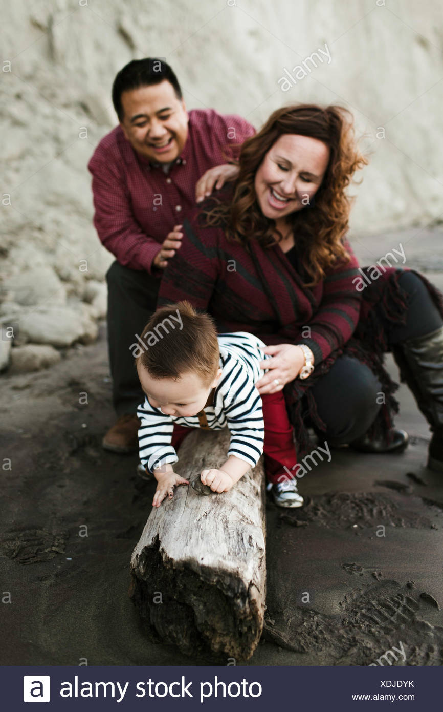 Family with baby boy sitting on driftwood on beach - Stock Image