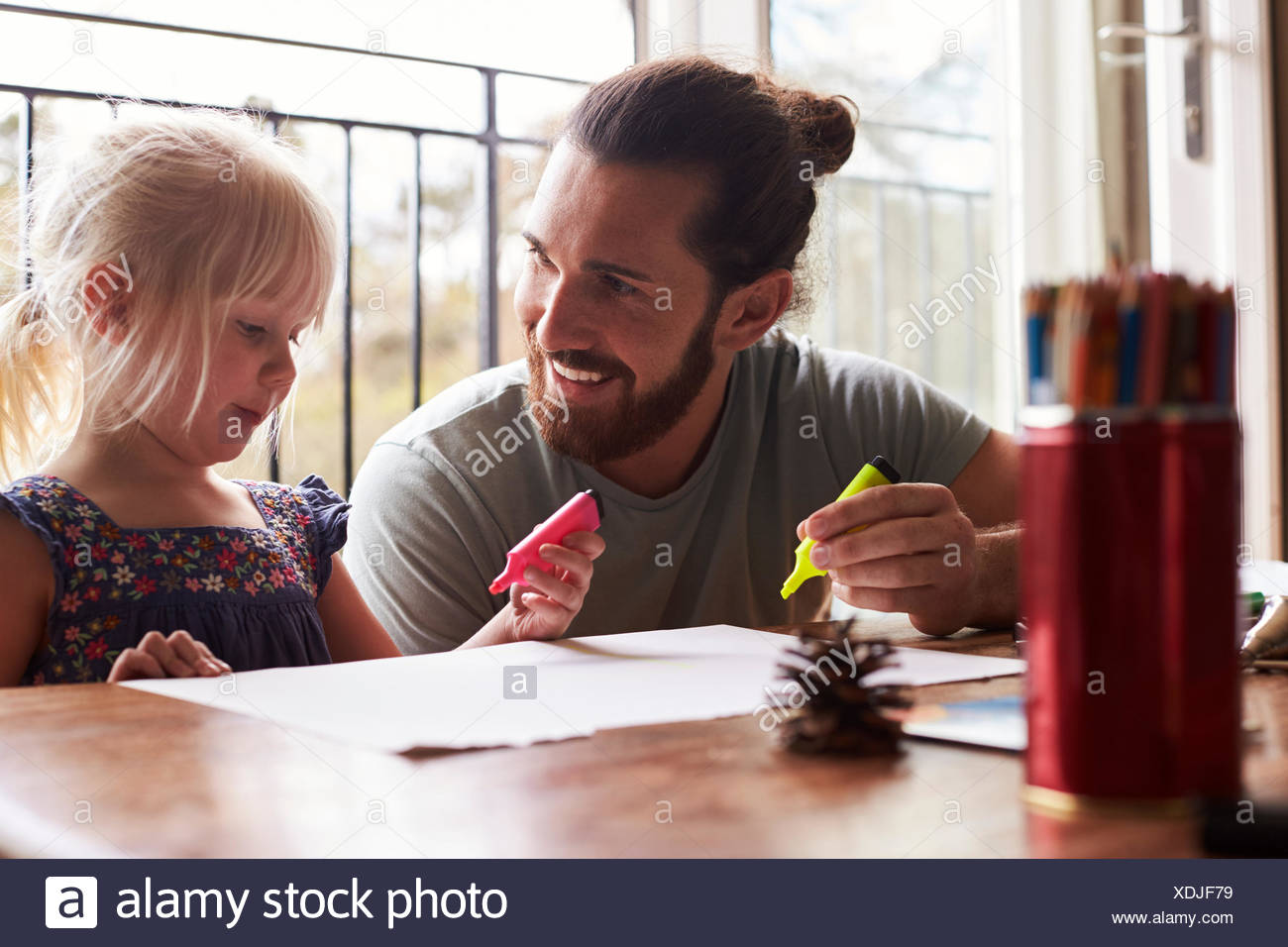 Father And Daughter Sitting At Table And Drawing Pictures - Stock Image