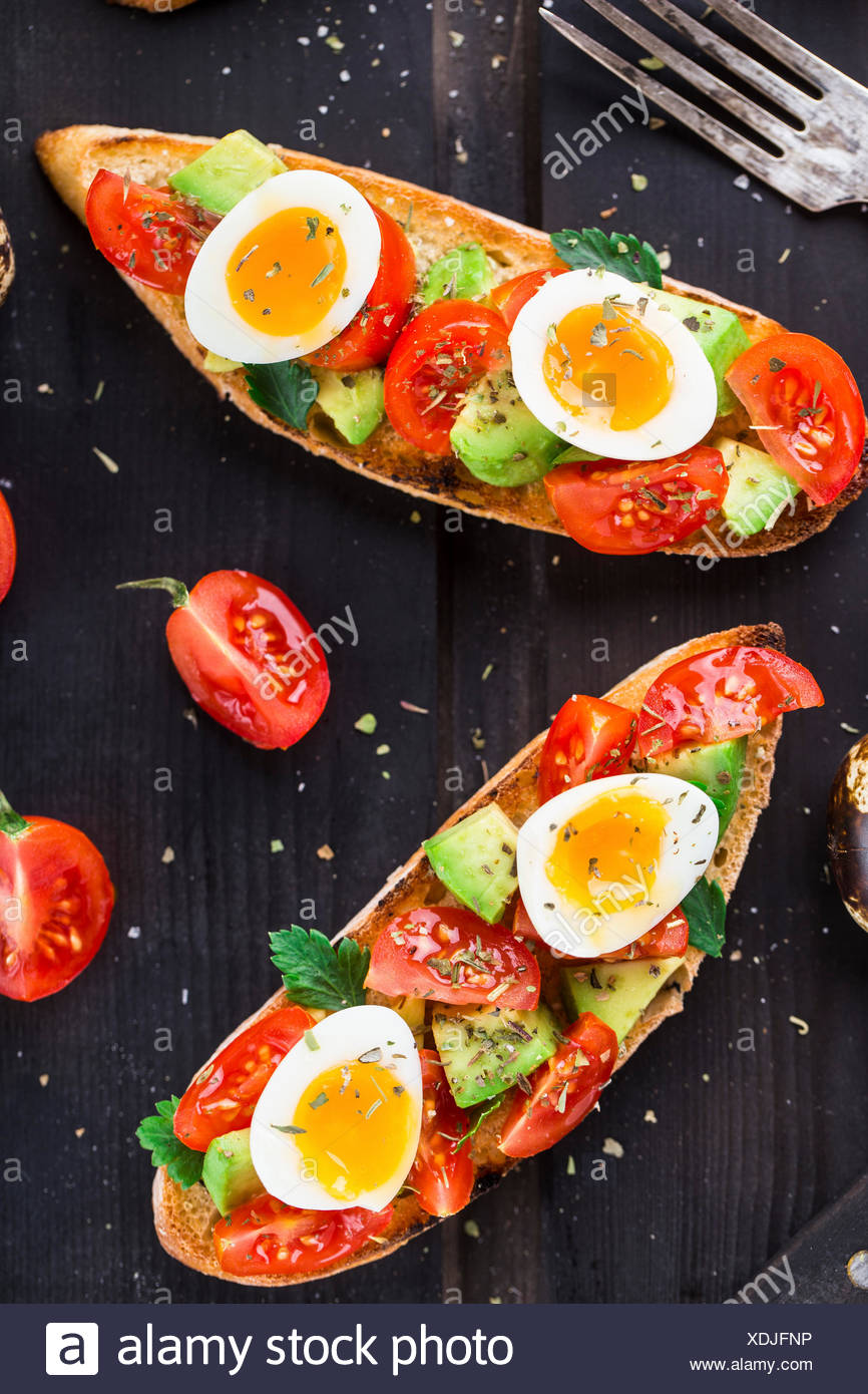 Bruschetta with tomato, avocado and quail egg on a wooden table - Stock Image