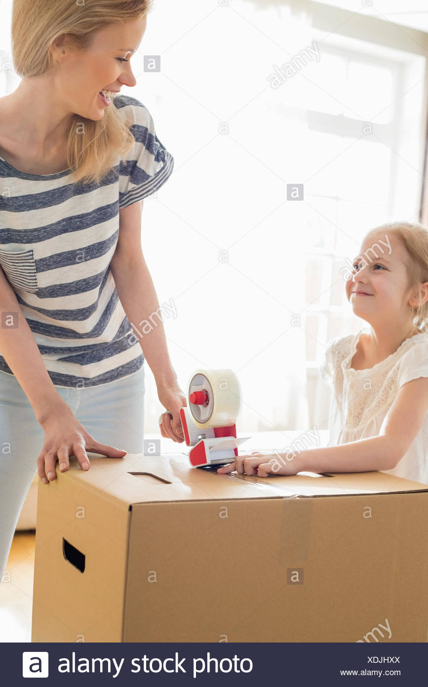 Mother and daughter looking at each other while packing cardboard box at home - Stock Image