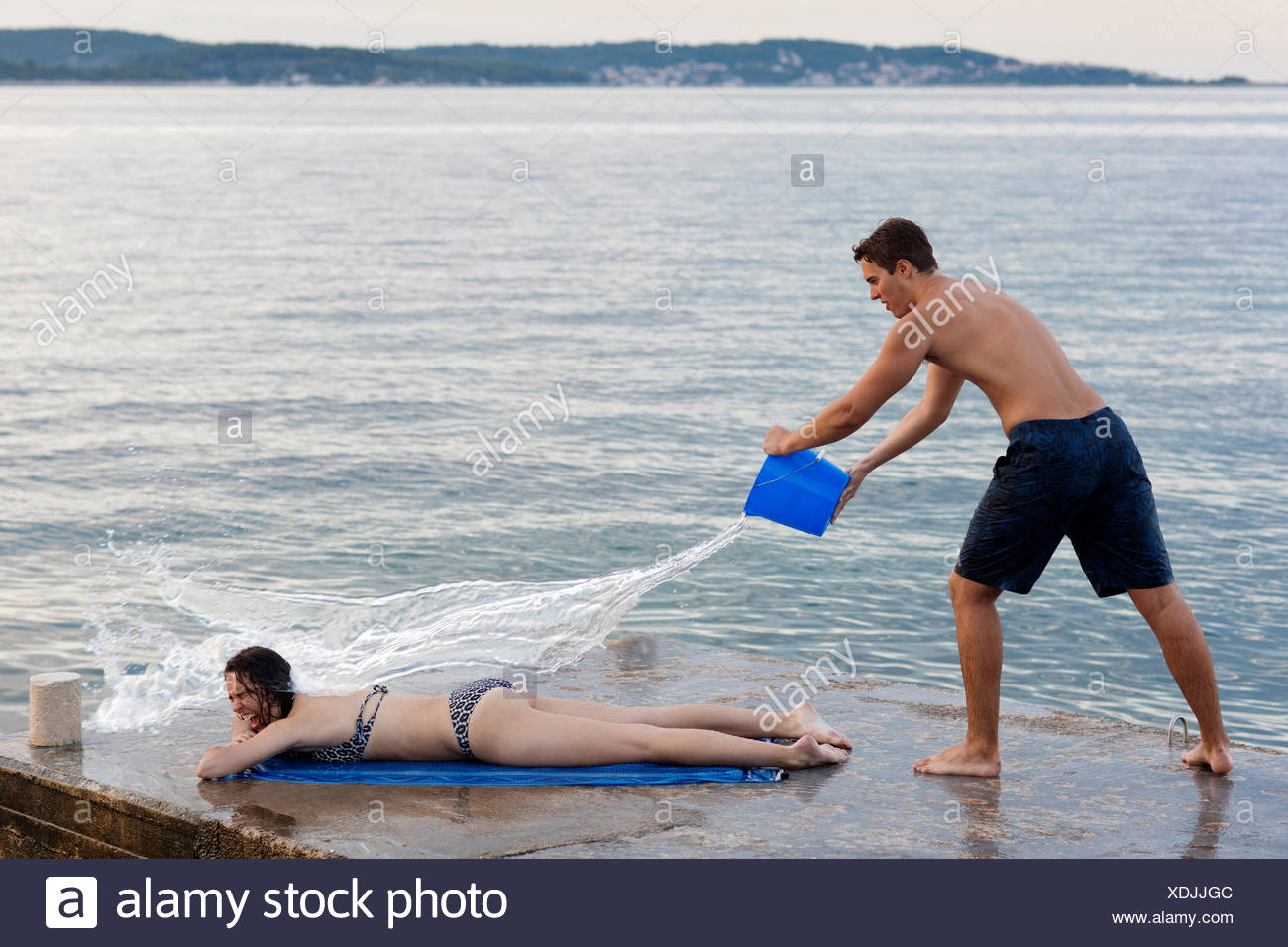 Young man throwing bucket of water over female sunbather, Orebic, Croatia Stock Photo