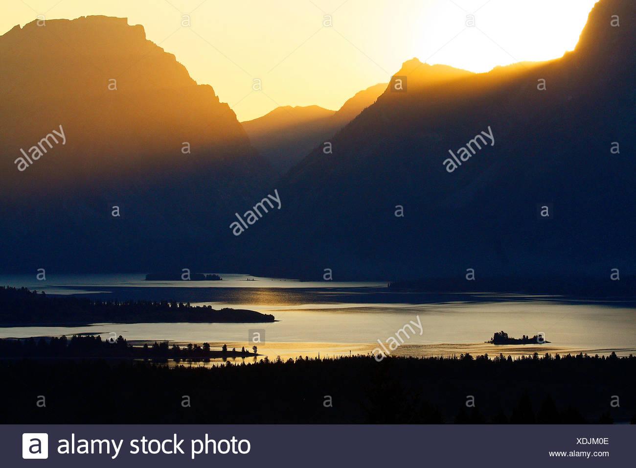 A setting sun shines over Jackson Lake and the Grand Tetons at Grand Teton National Park, Wyoming - Stock Image