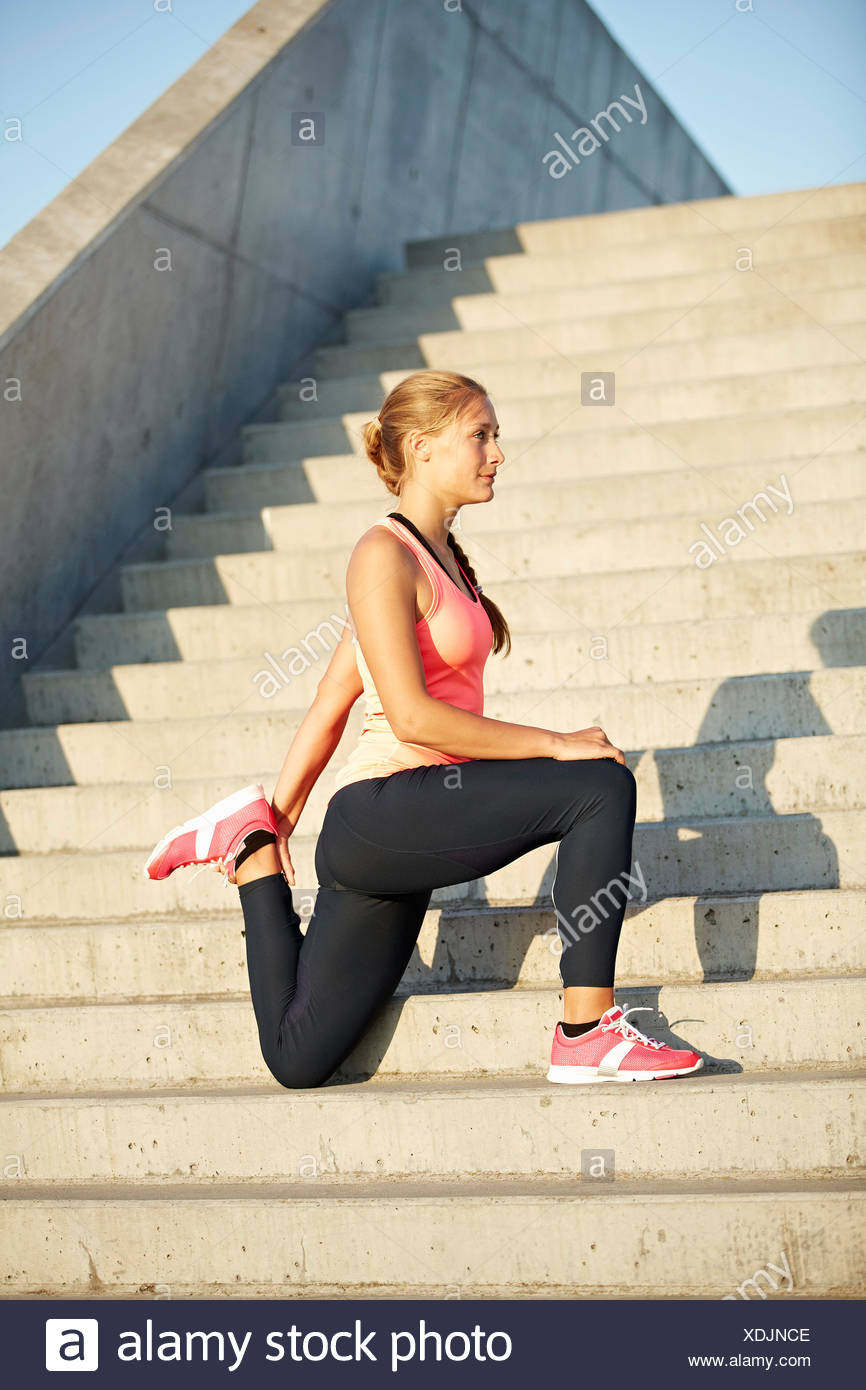 Runner stretching on staircase Stock Photo