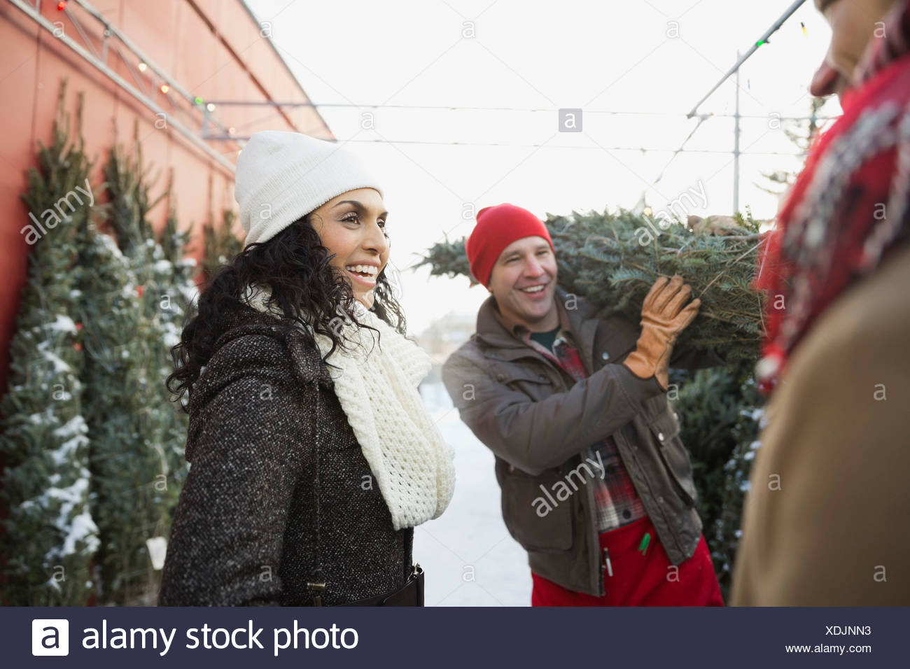Woman with tree lot owner carrying Christmas tree - Stock Image