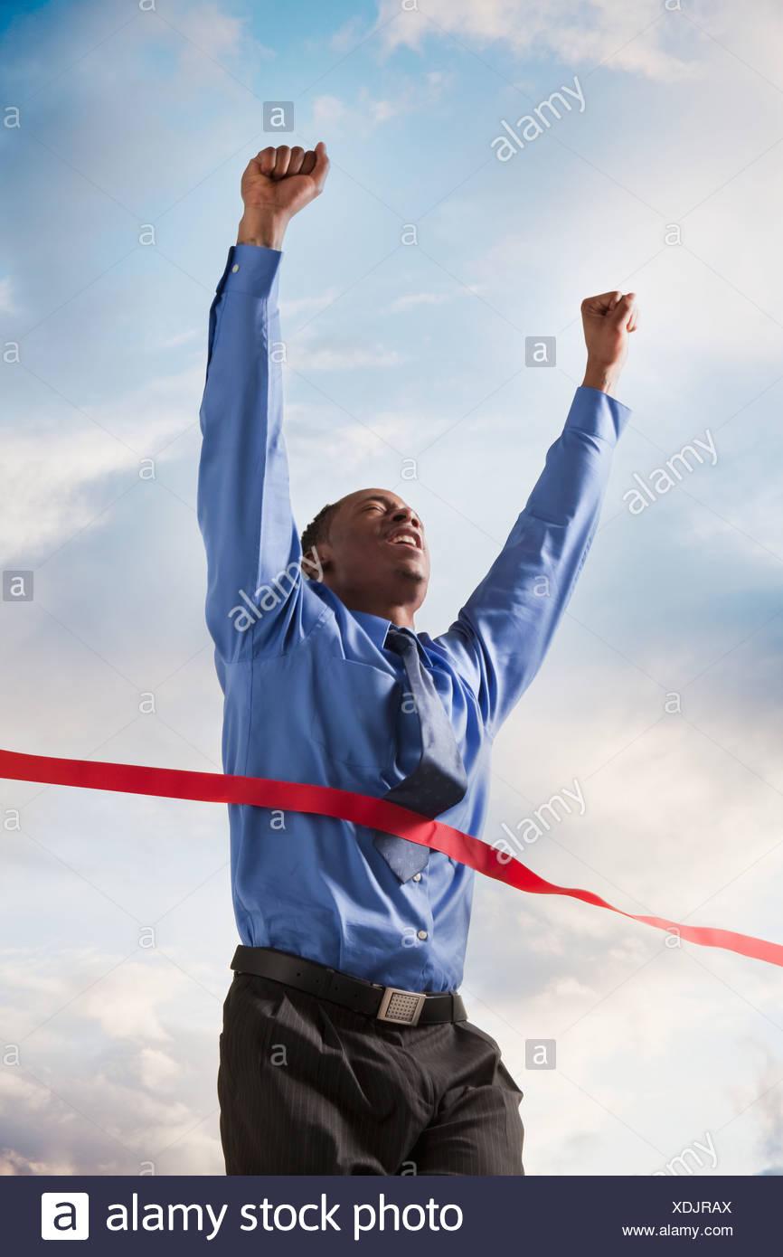 Businessman winning a race - Stock Image