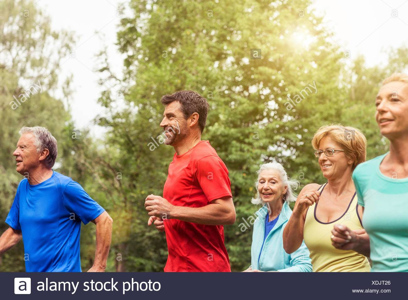 Group of adults running outdoors - Stock Image