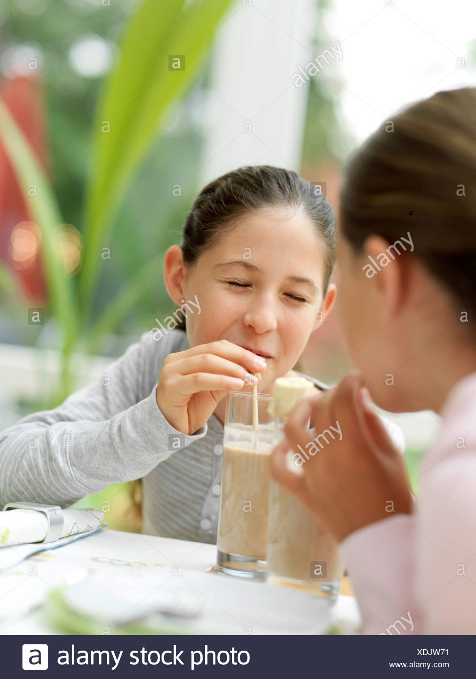 Two girls drinking chocolate milk with straw - Stock Image