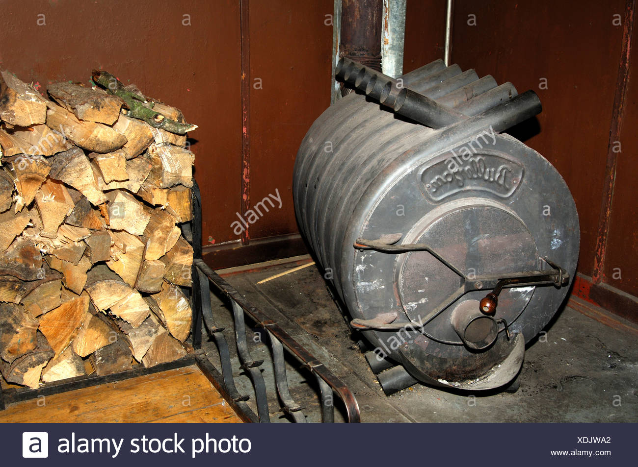 Hot air furnace Bullerjan and a heap of firewood logs - Stock Image