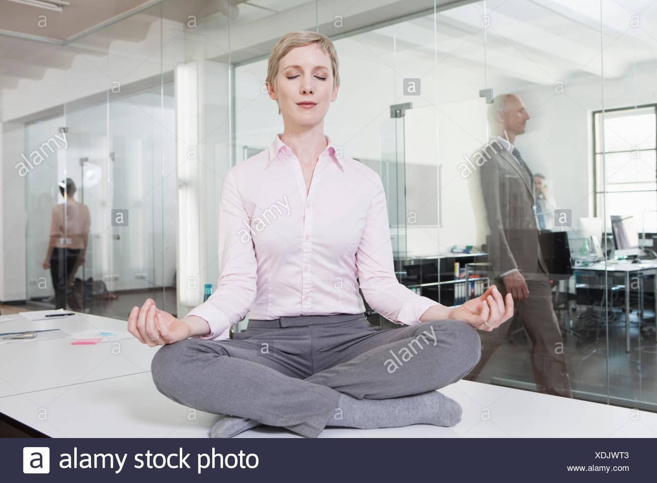 meditation office. Germany, Munich, Businesswoman In Office, Meditating On Desk - Stock Image Meditation Office L