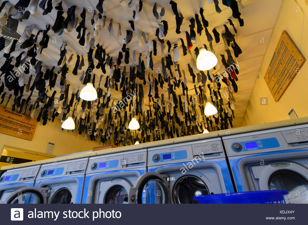 laundrette in the Äußere Neustadt, in the washing machin forgotten socks hanging from the ceiling, Germany, Saxony, Dresden - Stock Image