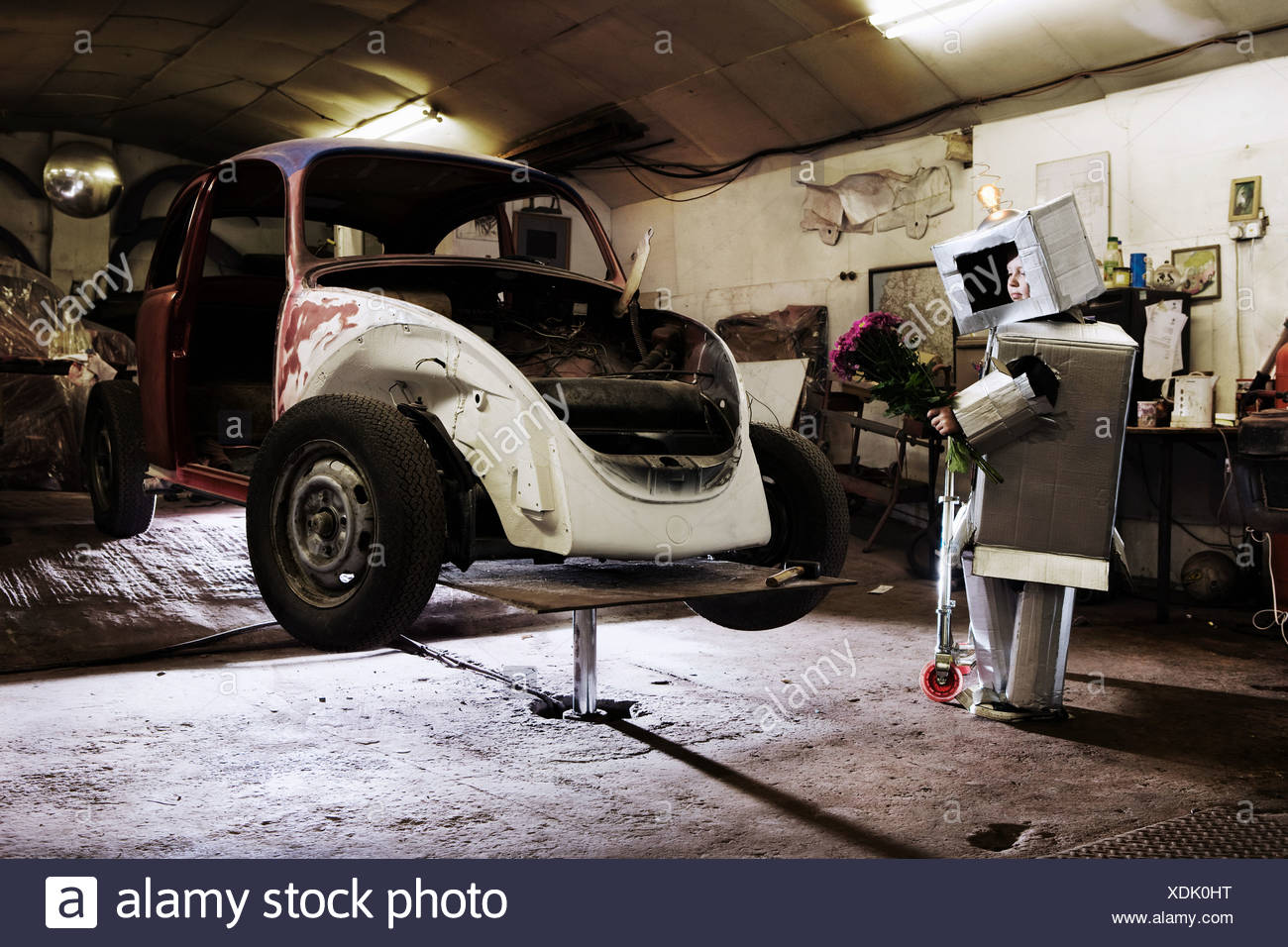 Boy dressed as robot holding bunch of flowers with old car in garage - Stock Image
