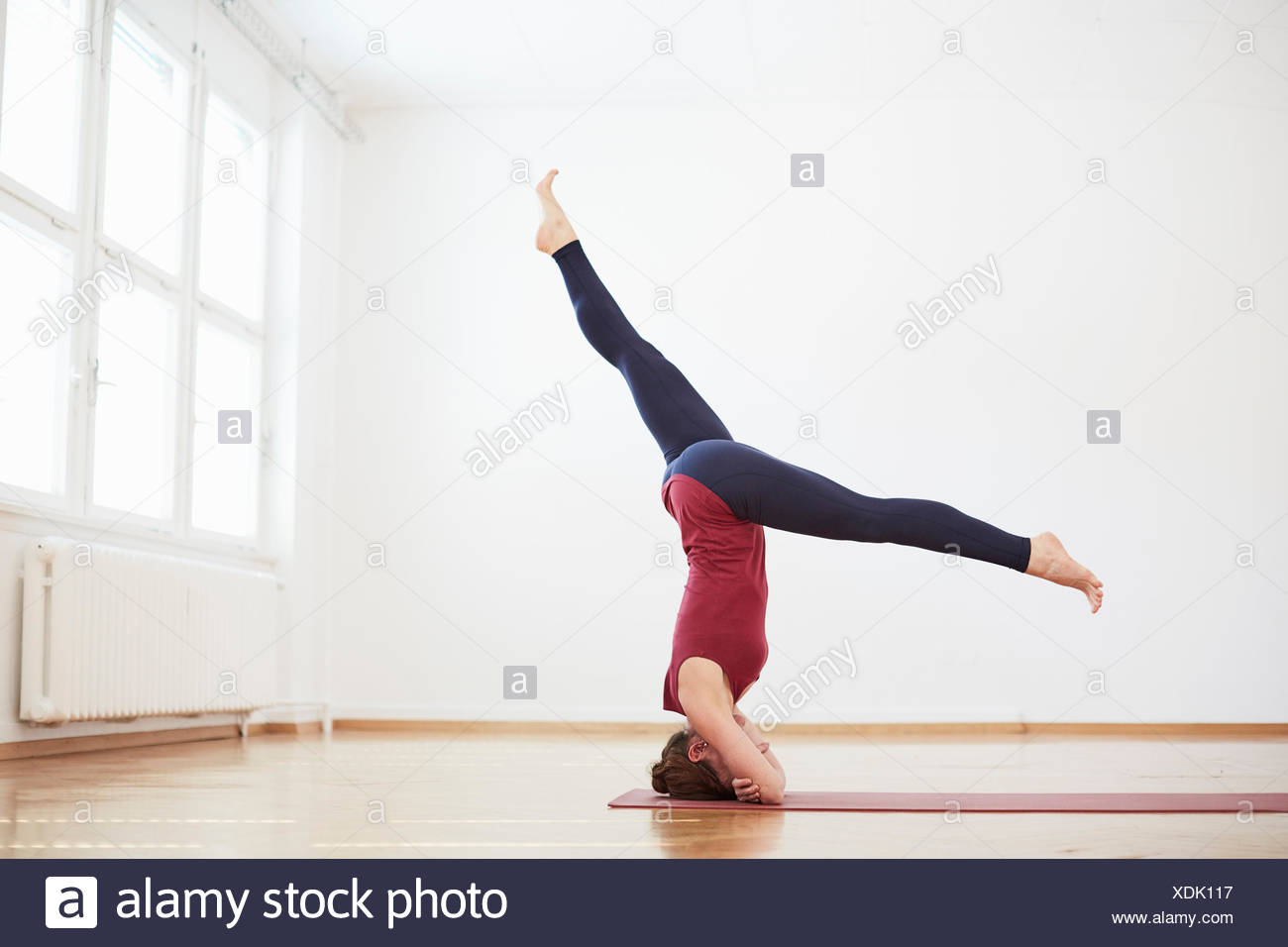 Woman in exercise studio legs apart doing headstand - Stock Image