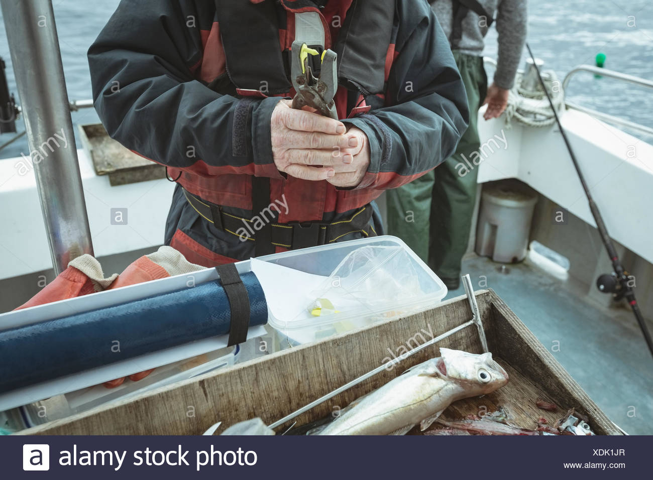 Fisherman pressing tag with hand tool - Stock Image