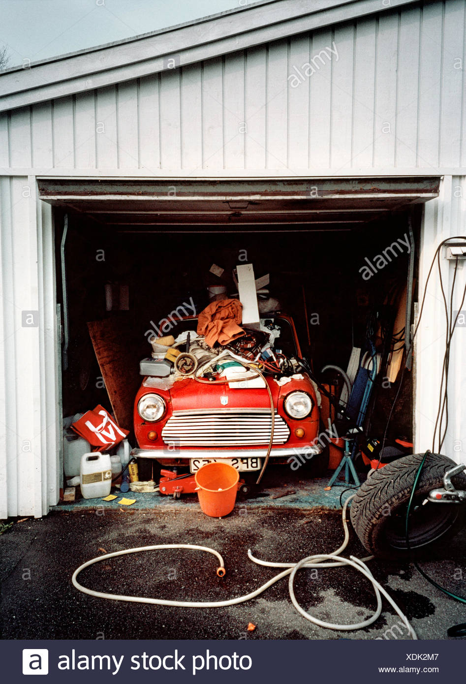 Old-fashioned car in messy garage - Stock Image