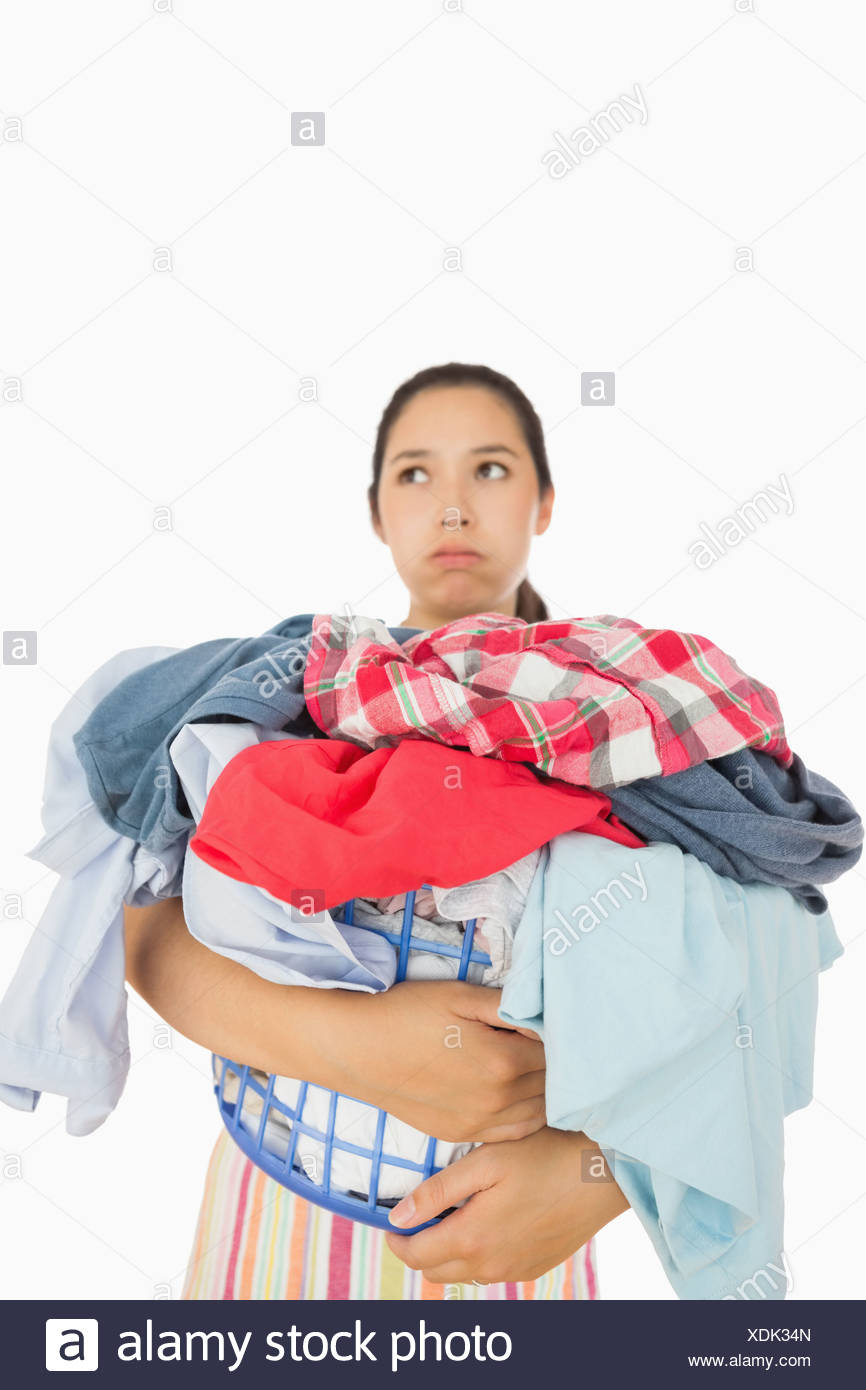 Overworked woman holding basket full of laundry - Stock Image