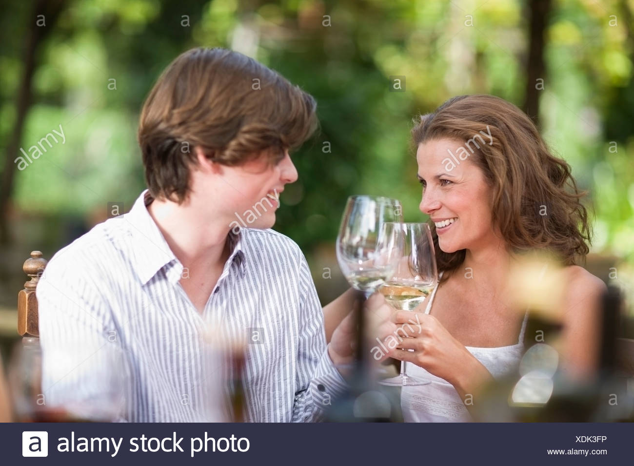 Woman and boy clinking  glasses - Stock Image