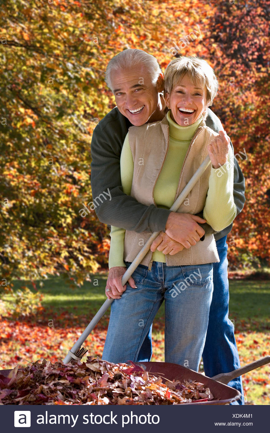Senior couple doing yard work in autumn - Stock Image