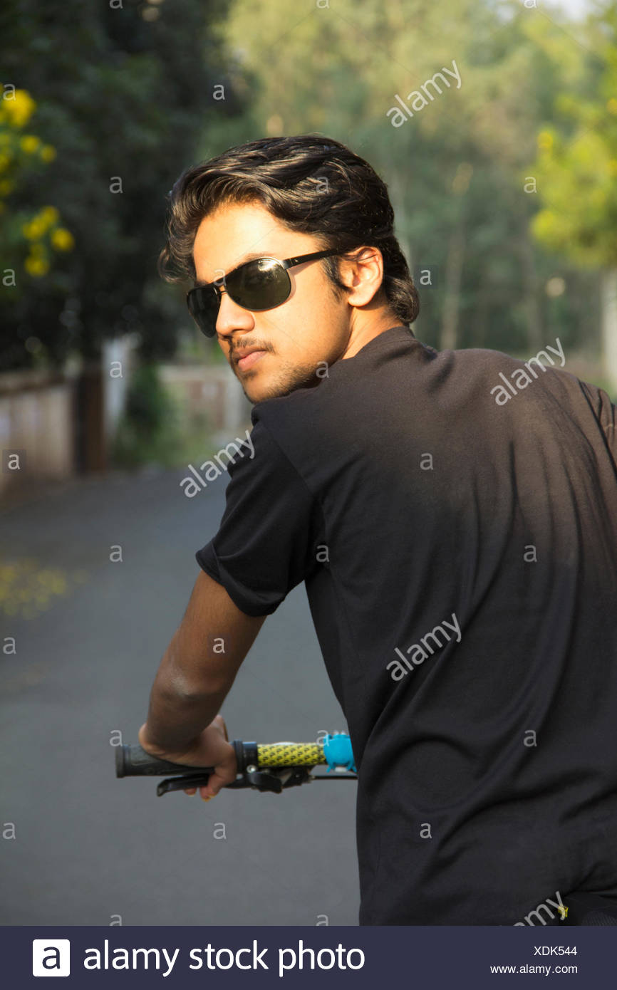 Young Indian boy wearing sun glasses and posing with bicycle - Stock Image