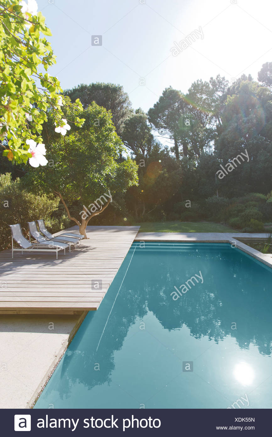 Wooden deck and lounge chairs by swimming pool - Stock Image