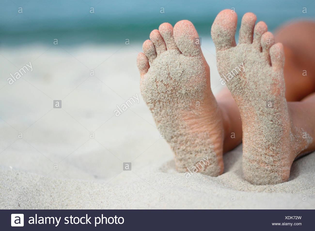 Italy, Sardinia, Person lying on beach, sandy feet - Stock Image
