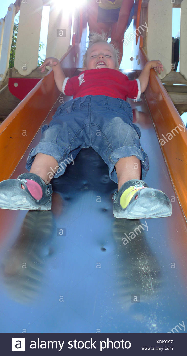 little boy happy on a slide - Stock Image