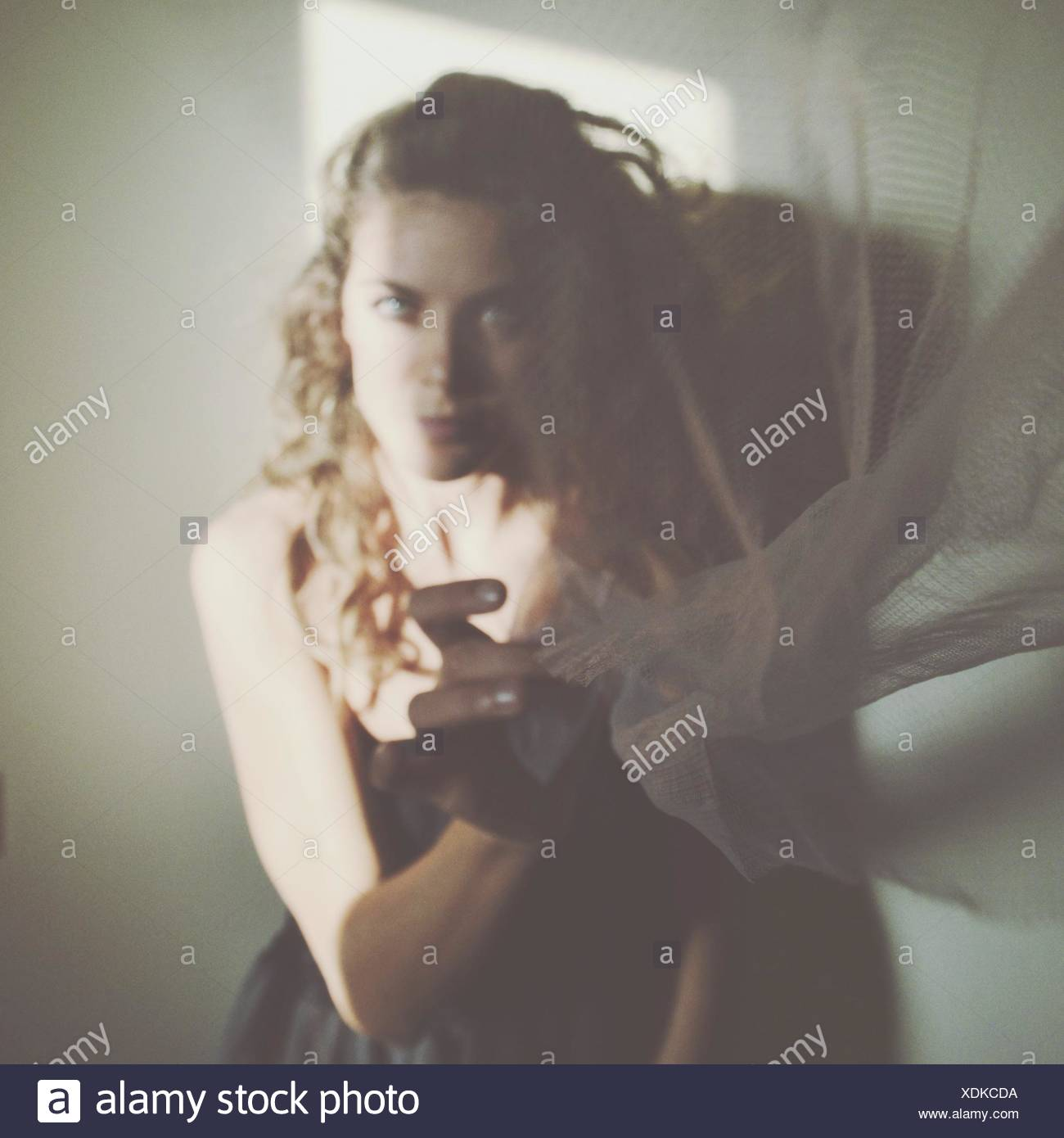 Portrait Of Young Woman Holding Transparent Fabric - Stock Image