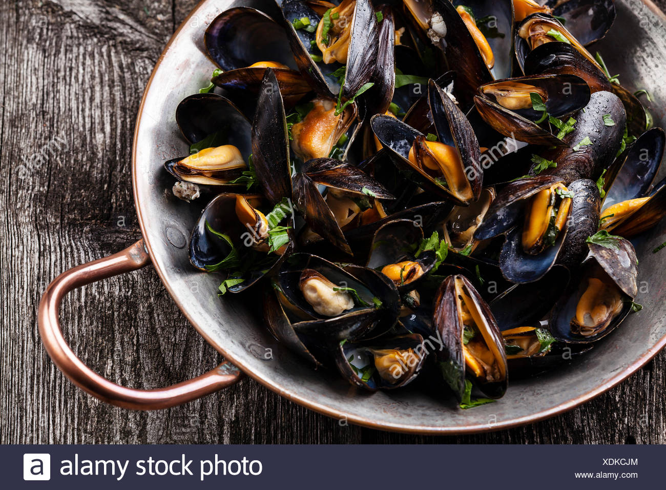 Boiled mussels in copper cooking dish on dark wooden background close up Stock Photo